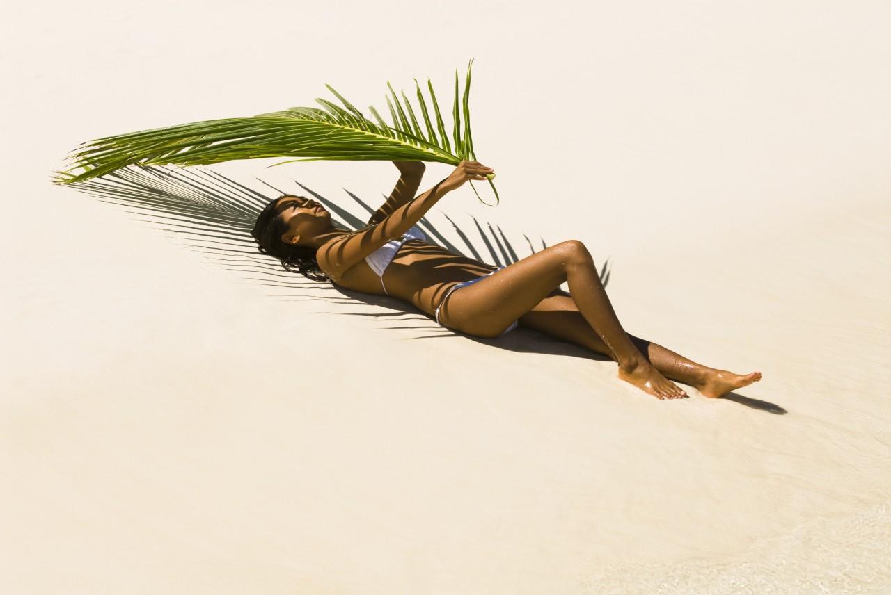 Femme bronze et se protège avec une feuille de palmier